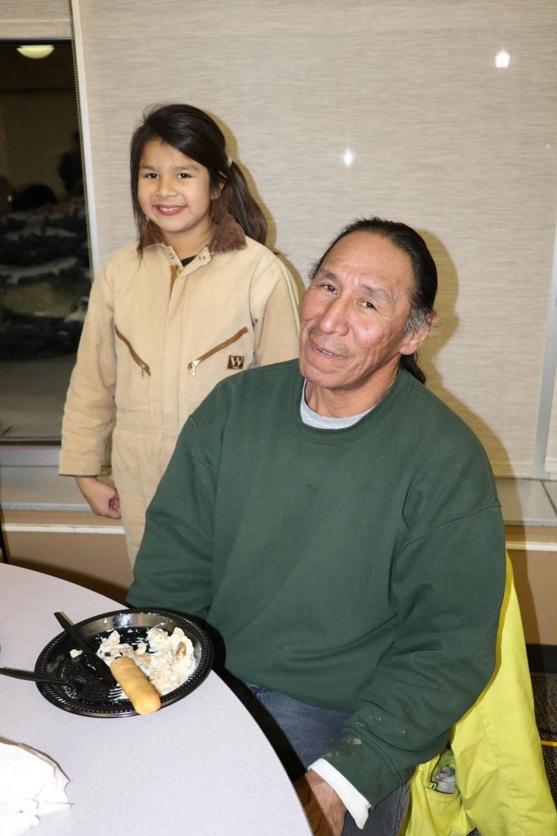 Dakota 38+2 staff carrier Wilfred Keeble and his eight-year-old granddaughter Ezmiah Middletent enjoying a meal at Dakota State University on Dec. 14.