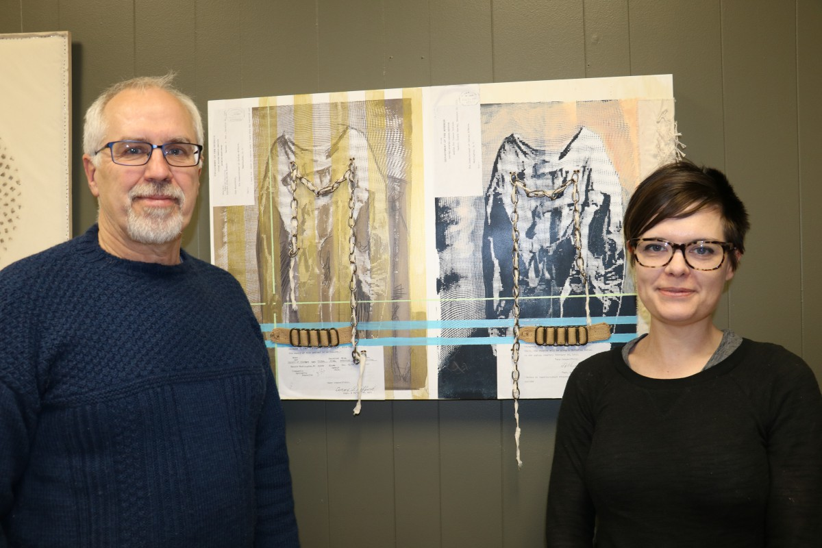 DSU English faculty Dr. John Nelson (left) and Dr. Stacey Berry pose by artwork inspired by the Hiawatha Indian Asylum.