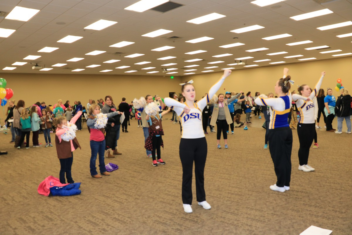Dakota State University basketball cheerleader Brittan Flanagan (left), Cass Coss, and Alexis Hanson lead area Girl Scouts in some cheers at last weekend's Cookie University, held on the DSU campus. The camp taught the scouts how to run their upcoming cookie sales businesses.