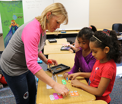 CybHER co-founder Pam Rowland helps two elementary students