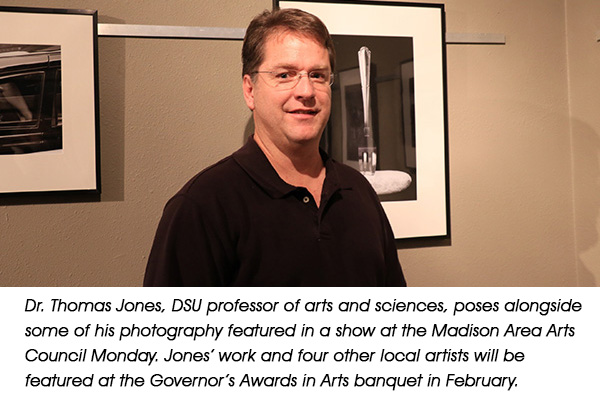 MOMENT IN TIME – Dr. Thomas Jones, DSU professor of arts and sciences, poses alongside some of his photography featured in a show at the Madison Area Arts Council Monday. Jones' work and four other local artists will be featured at the Governor's Awards in Arts banquet in February.
