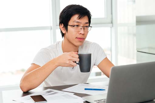 Software development student having coffee while working on a project